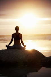 Woman Meditating at Sunset